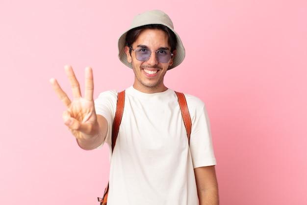 Jeune homme hispanique souriant et semblant amical, montrant le numéro trois. concept d'été