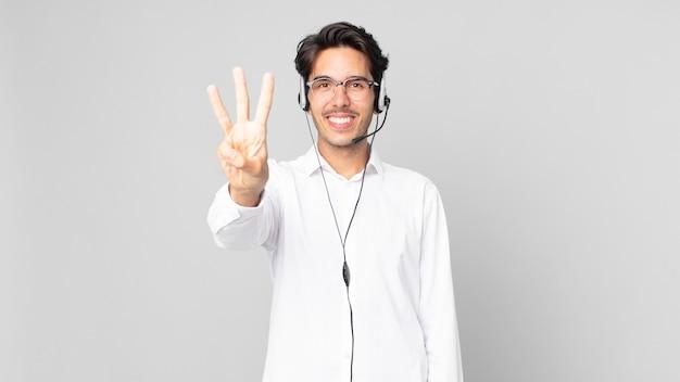 Jeune homme hispanique souriant et semblant amical, montrant le numéro trois. concept de télévendeur