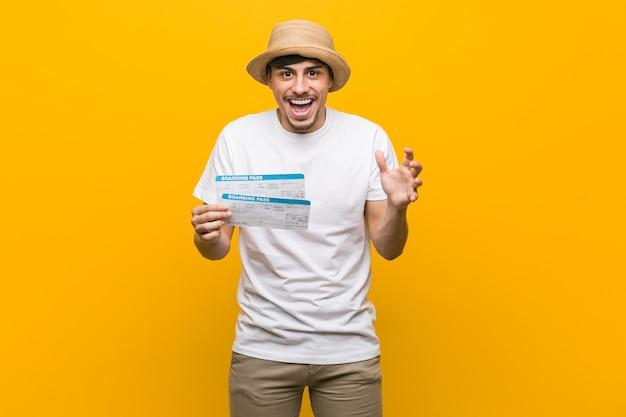 Jeune homme hispanique tenant un billet d'avion célébrant une victoire ou un succès