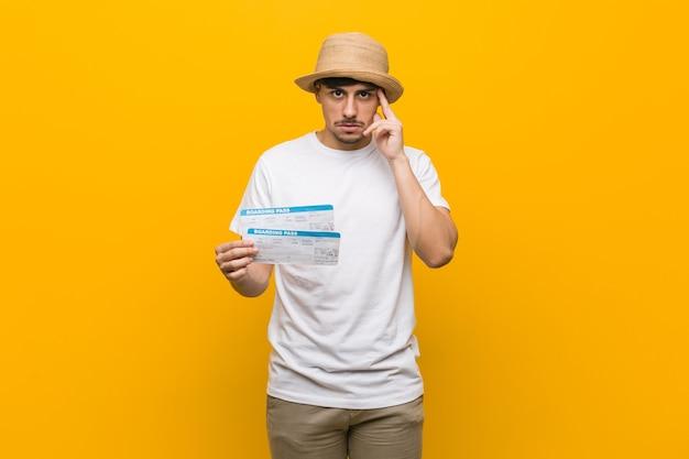 Jeune homme hispanique tenant un billet d'avion pointant sa tempe avec le doigt, pensant, concentré sur une tâche.