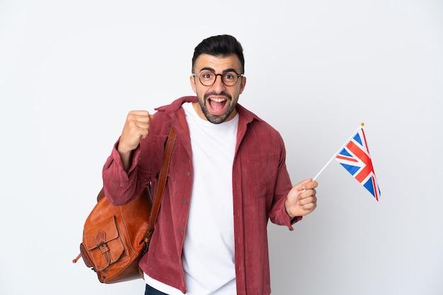 Jeune homme hispanique tenant un drapeau du royaume-uni célébrant une victoire en position de vainqueur