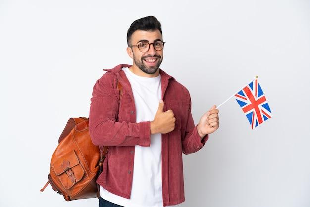 Jeune homme hispanique tenant un drapeau du royaume-uni donnant un geste de pouce en l'air