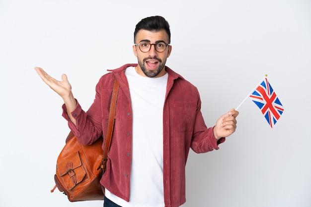 Jeune homme hispanique tenant un drapeau du royaume-uni avec une expression faciale choquée