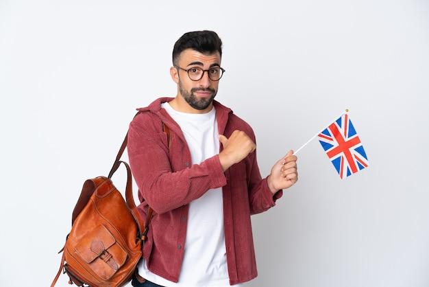 Jeune homme hispanique tenant un drapeau du royaume-uni fier et satisfait de soi