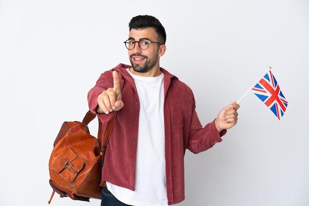 Jeune homme hispanique tenant un drapeau du royaume-uni montrant et en soulevant un doigt