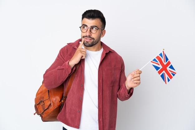 Jeune homme hispanique tenant un drapeau du royaume-uni en pensant à une idée tout en regardant