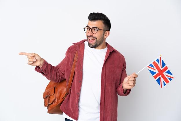 Jeune homme hispanique tenant un drapeau du royaume-uni pointant le doigt sur le côté et présentant un produit
