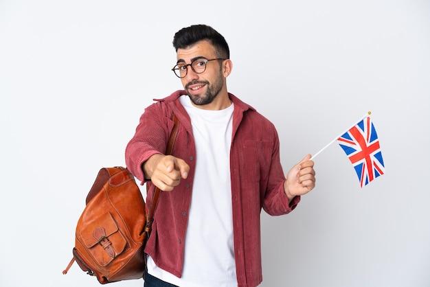 Jeune homme hispanique tenant un drapeau du royaume-uni pointant vers l'avant avec une expression heureuse