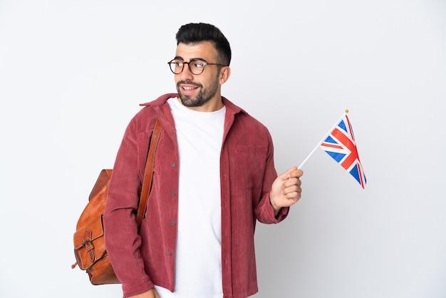 Jeune homme hispanique tenant un drapeau du royaume-uni à la recherche sur le côté et souriant