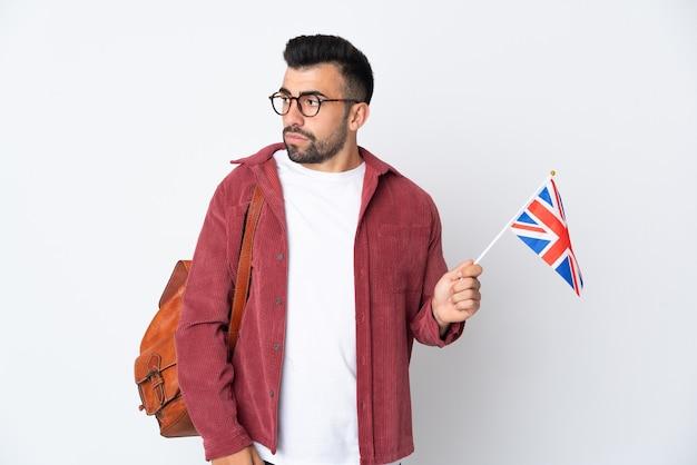 Jeune homme hispanique tenant un drapeau du royaume-uni à la recherche sur le côté