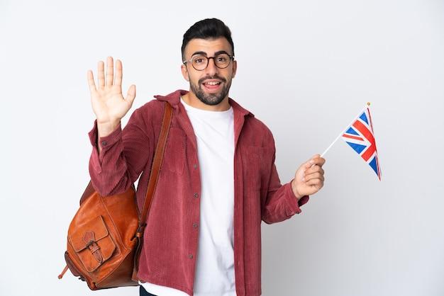 Jeune homme hispanique tenant un drapeau du royaume-uni saluant avec la main avec une expression heureuse