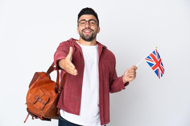 Jeune homme hispanique tenant un drapeau du royaume-uni se serrant la main