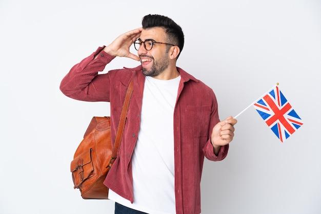 Jeune homme hispanique tenant un drapeau du royaume-uni souriant beaucoup