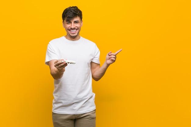 Jeune homme hispanique tenant une icône d'avion souriant joyeusement pointant avec l'index.