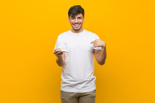Jeune homme hispanique tenant une icône d'avion surpris en se montrant, souriant largement.