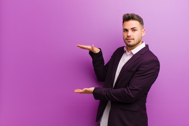 Jeune homme hispanique tenant un objet à deux mains sur l'espace de copie, montrant, offrant ou annonçant un objet