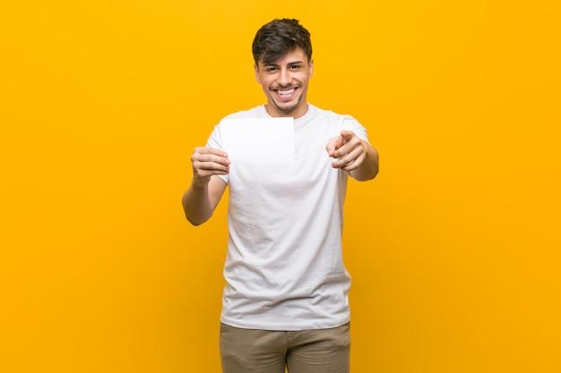 Jeune homme hispanique tenant une pancarte de joyeux sourires pointant vers l'avant.