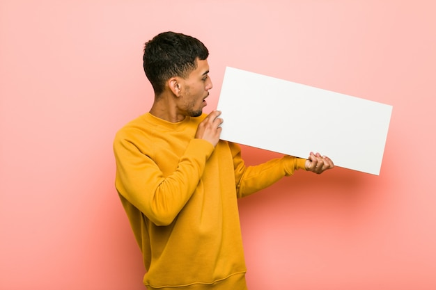 Jeune homme hispanique tenant une pancarte