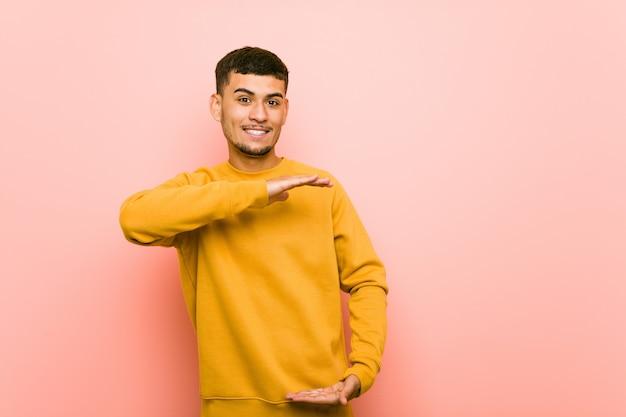 Jeune homme hispanique tenant quelque chose à deux mains, présentation du produit.