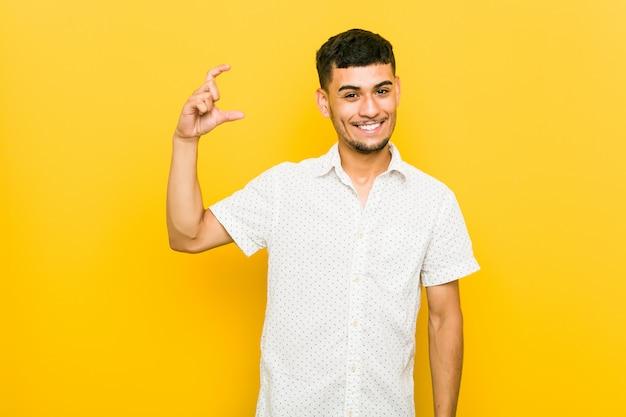 Jeune homme hispanique tenant quelque chose de petit avec les index, souriant et confiant.