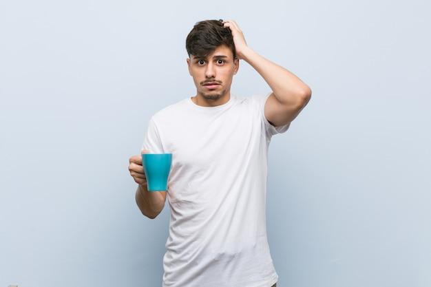 Jeune homme hispanique tenant une tasse en état de choc, elle s'est souvenue d'une réunion importante.