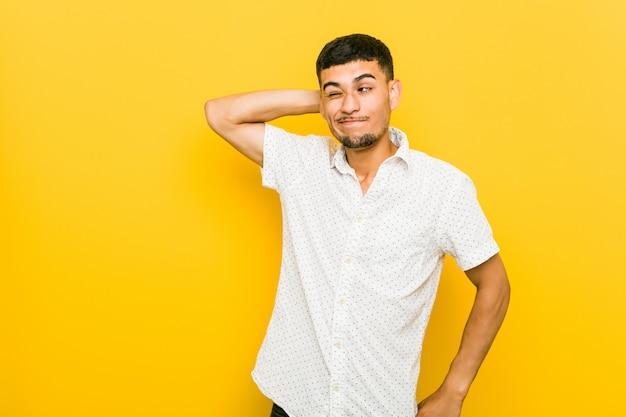 Jeune homme hispanique touchant l'arrière de la tête, réfléchissant et faisant un choix.