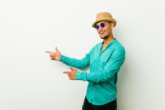 Jeune homme hispanique vêtu d'un vêtement d'été excité, pointant du doigt avec l'index.