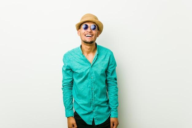 Jeune homme hispanique vêtu d'un vêtement d'été rit et ferme les yeux, se sent détendu et heureux.