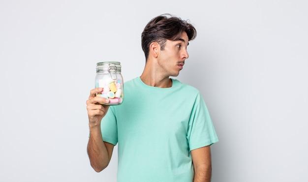 Jeune homme hispanique sur la vue de profil pensant, imaginant ou rêvant. concept de bonbons à la gelée