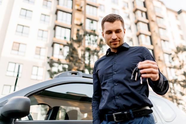 Un jeune homme ou un homme d'affaires en chemise sombre se tient dans la rue près de la voiture et regardera les clés de la voiture. le chauffeur attend son passager ou son client. concept de transport urbain