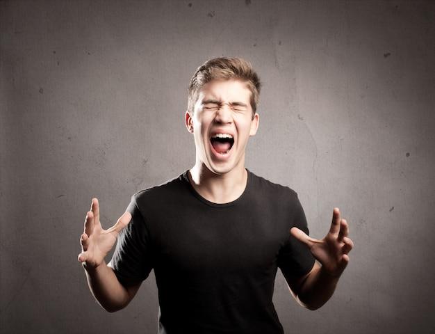 Jeune homme hurlant sur un fond gris