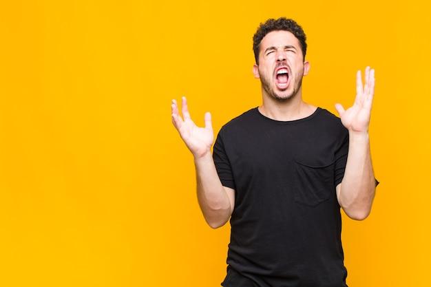 Jeune homme hurlant furieusement, se sentant stressé et agacé avec les mains en l'air en disant pourquoi moi