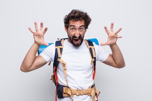 Jeune homme hurlant de panique ou de colère, choqué, terrifié ou furieux, avec les mains à côté de la tête