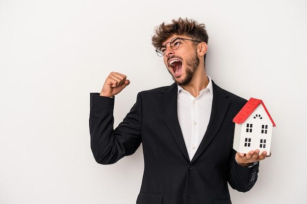 Jeune homme immobilier arabe tenant une maison modèle isolée sur fond isolé levant le poing après une victoire, concept gagnant.