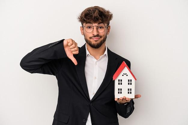 Jeune homme immobilier arabe tenant une maison modèle isolée sur fond isolé montrant un geste d'aversion, les pouces vers le bas. notion de désaccord.