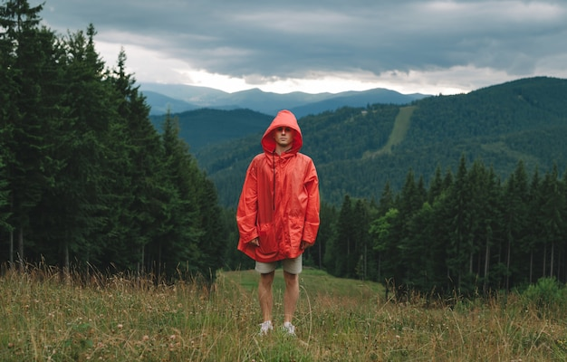 Jeune homme en imperméable rouge se dresse dans les montagnes par mauvais temps pluvieux