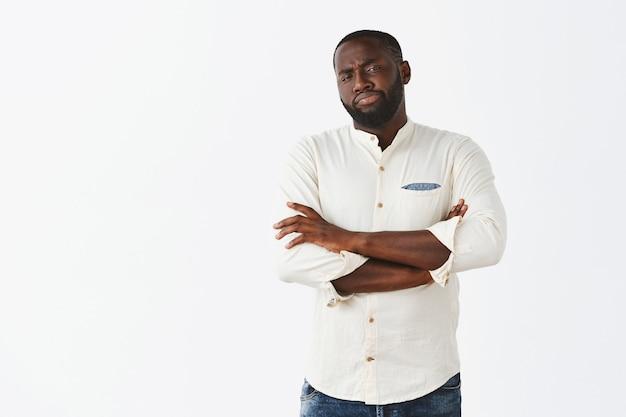 Jeune homme indécis et douteux posant contre le mur blanc