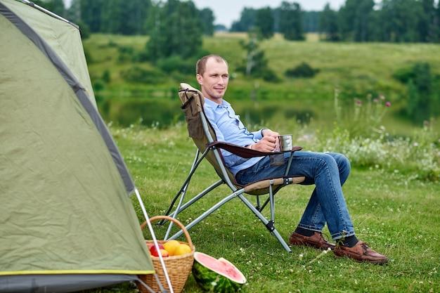 Jeune homme indépendant assis sur une chaise et se reposant devant une tente au camping en forêt ou dans un pré. activité de plein air en été. voyage d'aventure dans le parc national. loisirs, vacances, détente