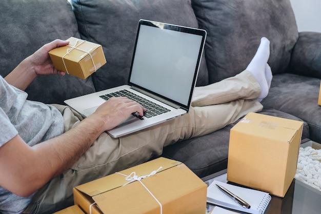 Jeune homme indépendant travaillant avec l'emballage de leurs colis sur le marché en ligne de livraison de boîtes