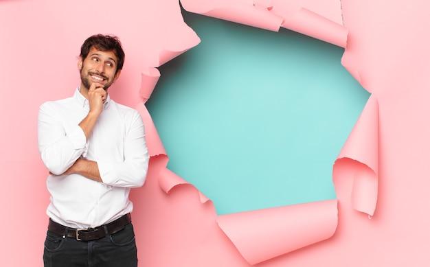 Jeune homme indien beau penser expression contre fond de trou de papier cassé