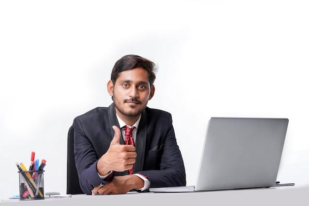 Jeune homme indien en costume, travaillant sur ordinateur portable et montrant des coups au bureau.