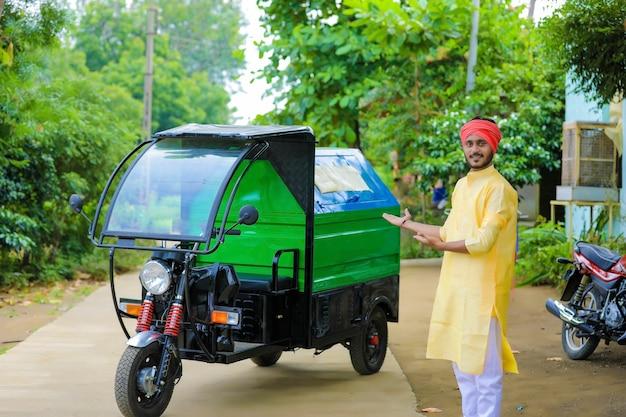 Jeune homme indien debout avec une camionnette