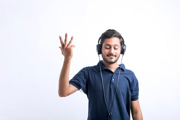 Jeune homme indien écoutant de la musique et montrant une expression sur fond blanc.