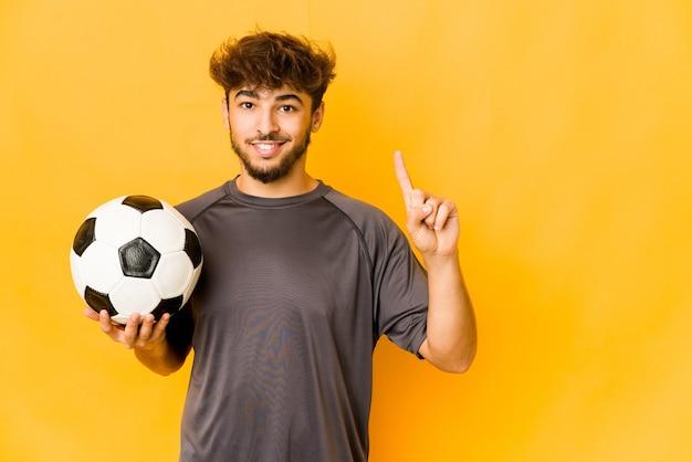 Jeune homme indien de footballeur montrant le numéro un avec le doigt.