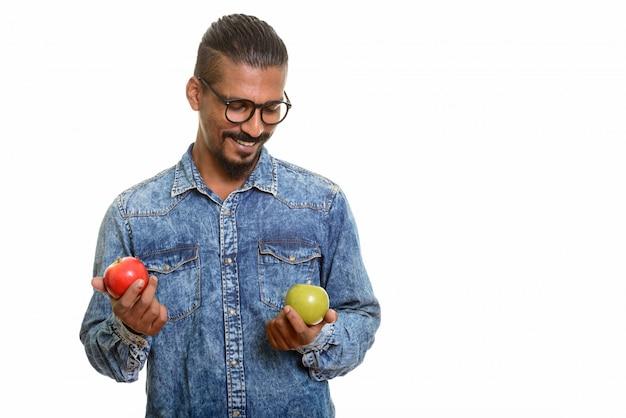Jeune homme indien heureux de choisir entre pomme rouge et verte isolée