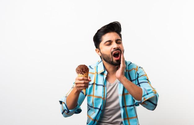 Jeune homme indien mangeant de la crème glacée dans un cône et ayant mal aux dents à cause de la cavité, assis à table sur fond jaune ou blanc