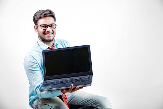 Jeune homme indien montrant l'écran d'ordinateur portable
