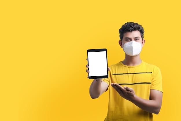 Jeune homme indien portant un masque et montrant une tablette