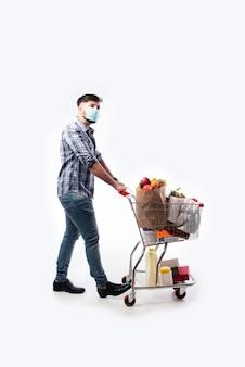Un jeune homme indien porte un masque facial transportant un caddie ou un chariot rempli d'épicerie, de légumes et de fruits. photo pleine longueur isolée sur mur blanc