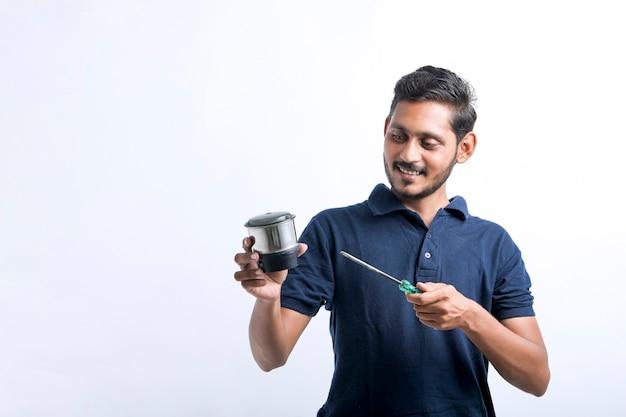 Jeune homme indien qui répare des ustensiles de cuisine électroniques tenant des outils à la main